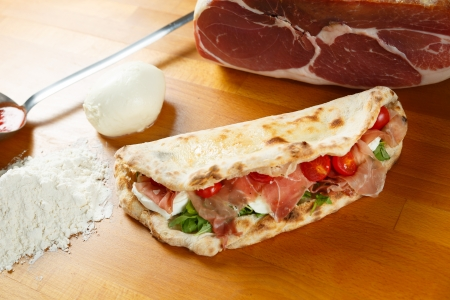 Typical Italian Pizza cooked in electric oven with ingredients in the background on a wood table Stock Photo - 17871219