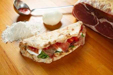 Typical Italian Pizza cooked in electric oven with ingredients in the background on a wood table Stock Photo - 17870473