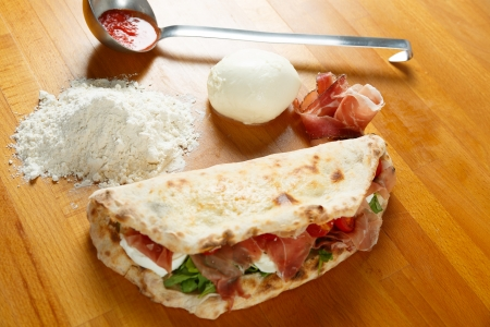 Typical Italian Pizza cooked in electric oven with ingredients in the background on a wood table Stock Photo - 17870479