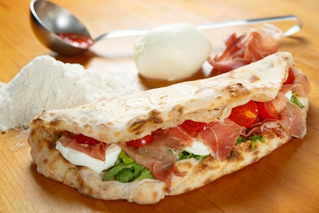 Typical Italian Pizza cooked in electric oven with ingredients in the background on a wood table Stock Photo - 17870640