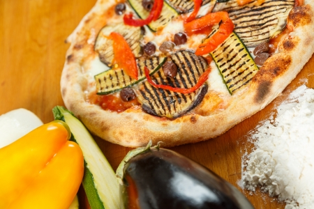 pizza maker: Typical Italian Pizza cooked in electric oven with ingredients in the background on a wood table