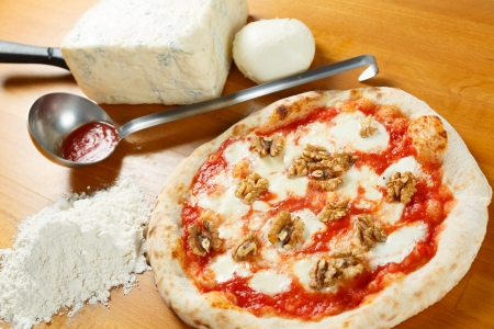 Typical Italian Pizza cooked in electric oven with ingredients in the background on a wood table Stock Photo - 17870373
