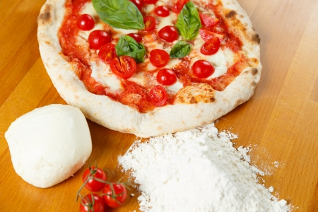 Typical Italian Pizza cooked in electric oven with ingredients in the background on a wood table