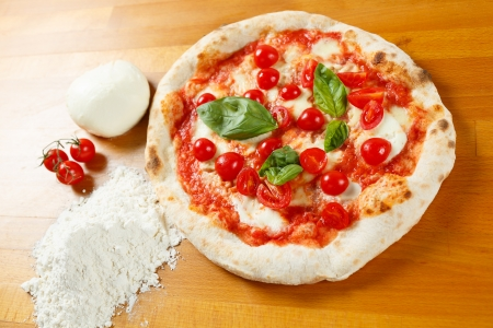 Typical Italian Pizza cooked in electric oven with ingredients in the background on a wood table Stock Photo - 17870482