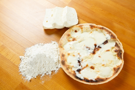 stracchino: Typical Italian Pizza cooked in electric oven with ingredients in the background on a wood table
