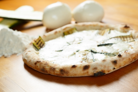 Typical Italian Pizza cooked in electric oven with ingredients in the background on a wood table Stock Photo - 17870585