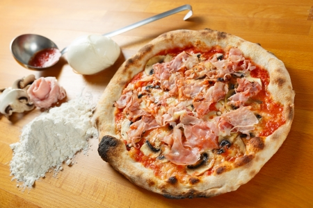 Typical Italian Pizza cooked in electric oven with ingredients in the background on a wood table Stock Photo - 17870369