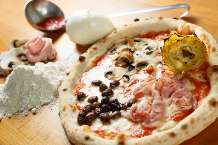 Typical Italian Pizza cooked in electric oven with ingredients in the background on a wood table Stock Photo - 17871068