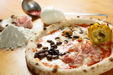 Typical Italian Pizza cooked in electric oven with ingredients in the background on a wood table Stock Photo - 17870872