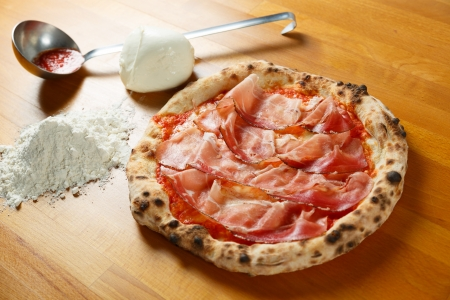 Typical Italian Pizza cooked in electric oven with ingredients in the background on a wood table Stock Photo - 17870237