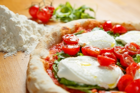 arugola: Typical Italian Pizza cooked in electric oven with ingredients in the background on a wood table