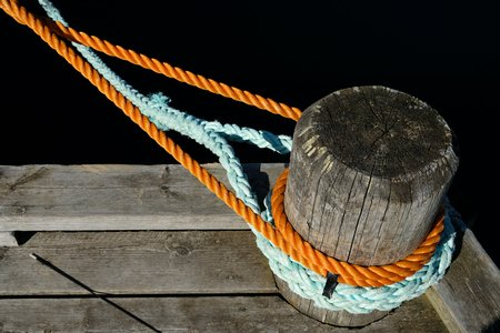 A mooring post with orange and light blue ship ropes attached to it