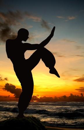 artes marciales: Arte marcial figura en la playa durante la puesta de sol