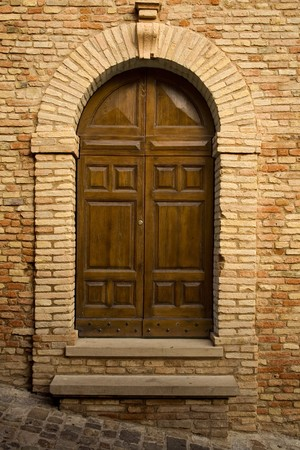 Ancient wooden door in stone archway and marble steps photo