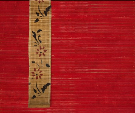 Flower bamboo banner on red ribbed wood textured background photo