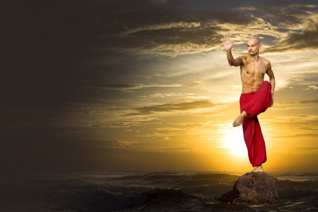 martial artist in red practices at sunset