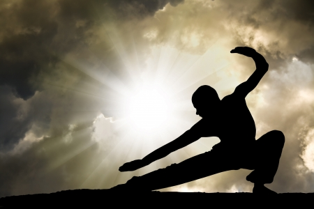 man practises martial arts with dramatic cloudy sky in background