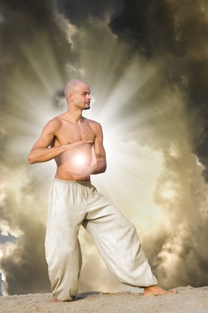 tai chi: man practises tai holding a ball of energy with dramatic cloudy sky and  sun rays in background