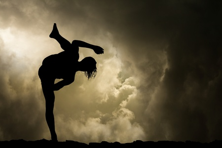 martial arts: Man Practises Martial Arts High Kick Silhouette on Stormy Sky Background Stock Photo