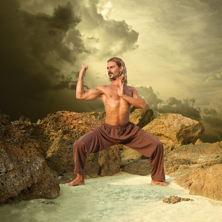 powerful young man trains in karate cloudy background Stock Photo - 9725113