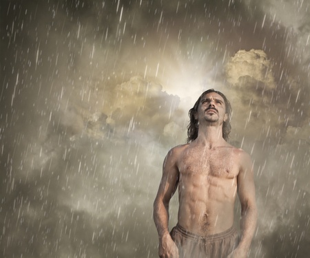 inclement: Man Feeling Lost in the Rain with a Ray of Hope breaking through the Clouds behind him