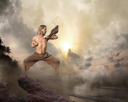 Man practices martial arts with bird of prey at dawn Standard-Bild