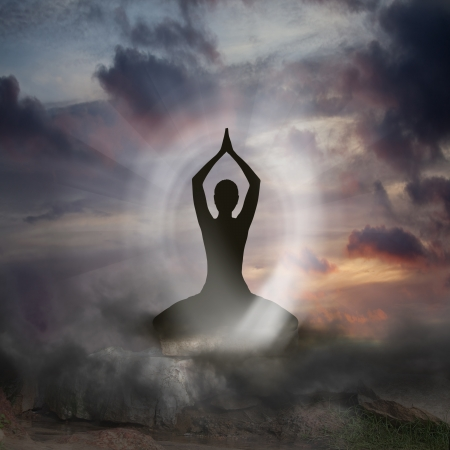 devotions: Silhouette of a Person practising Yoga and Spirituality Stock Photo