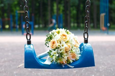 Wedding bouquet on blue swing in park