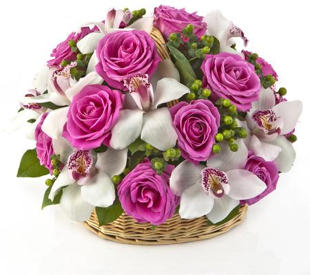 흰색 배경에 바구니에 분홍색 장미와 lilias의 꽃다발