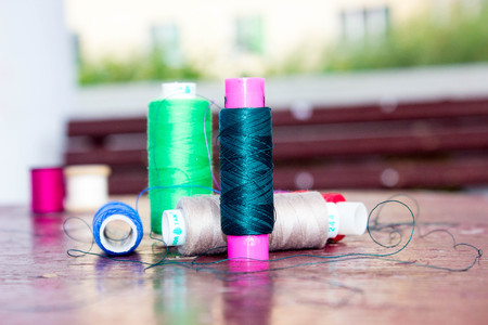 colored thread on wooden background texture