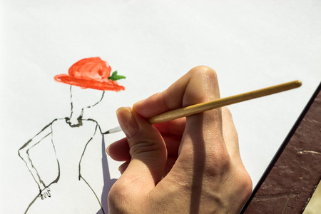 teaches: the artist teaches painting with a brush and watercolor of a woman on a conventional album sheet Stock Photo