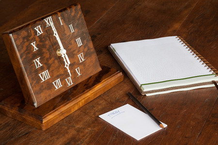 notations: wooden clock on the table, with paper to notations and pencil - 06:00 oclock