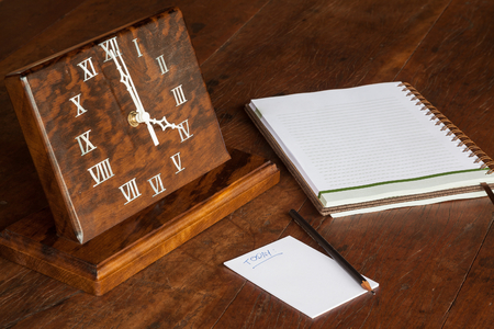 roman blind: wooden clock on the table, with paper to notations and pencil - 04:00 oclock