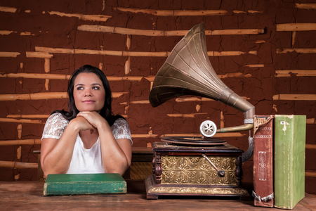 78 rpm: A girl listening to music on an old gramophone with some album discs on the table Stock Photo