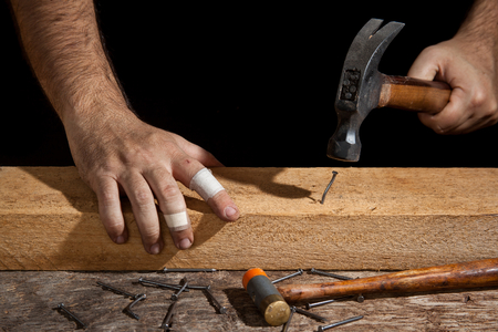 bent: A craftsman hammering bent nail with difficulty