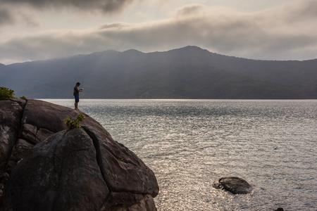 fishingpole: Man fishing on the rock Stock Photo