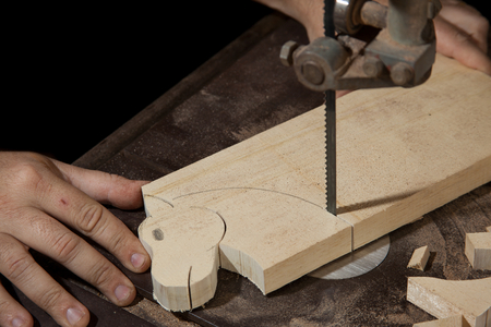 cutting horse: A craftsman cutting a wood head horse with bandsaw
