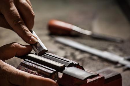 Luthier making a classical guitar bridge plate