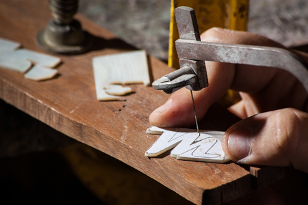 inlay: Luthier cutting a M letter mop inlay Stock Photo