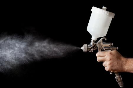 pistolas: Primer plano de una pistola de pintura en aerosol con el fondo negro Foto de archivo