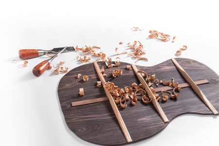 chisels: Back of guitar under construction with chisels and wood chips