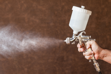 paint gun: Close up of a spray paint gun with brown background
