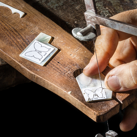 inlay: Craftsman cutting a piece of butterfly mop inlay Stock Photo