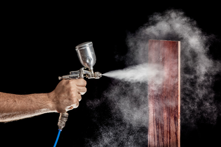 Close up of a spray paint gun with brown background