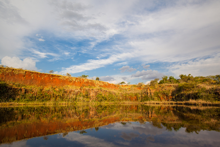 Reflexive lake with blue sky, clouds and green vegetation