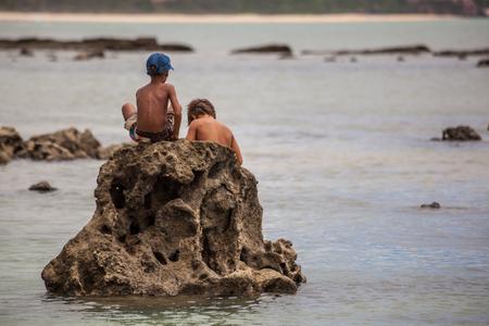 fishingpole: Two boys fishing on the coral at beach - Natal - Rio Grande do Norte - Brazil Stock Photo
