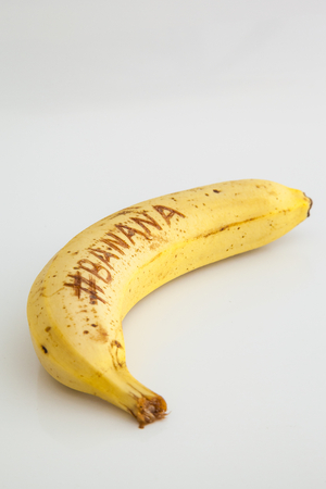 Banana with white background and text on fruit