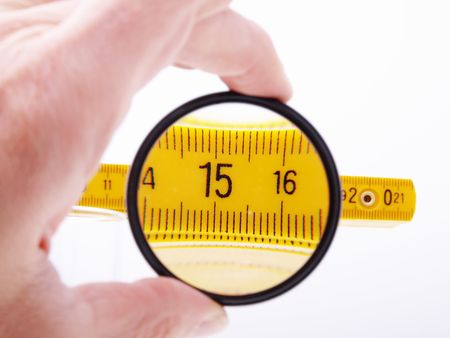 15 inch: Kind on a measuring ruler through magnifying glass