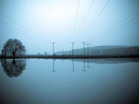 siloette: power line and mirror on pond Stock Photo