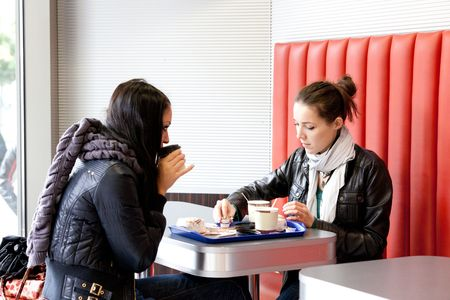 Two girls drink coffee in cafe in the winter photo